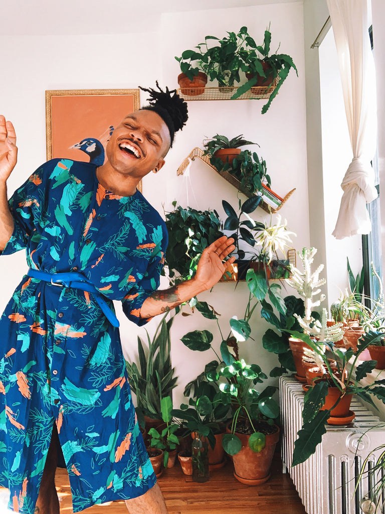 Christopher AKA the Plant Kween wears a blue tunic dress with a hand-printed botanical motif