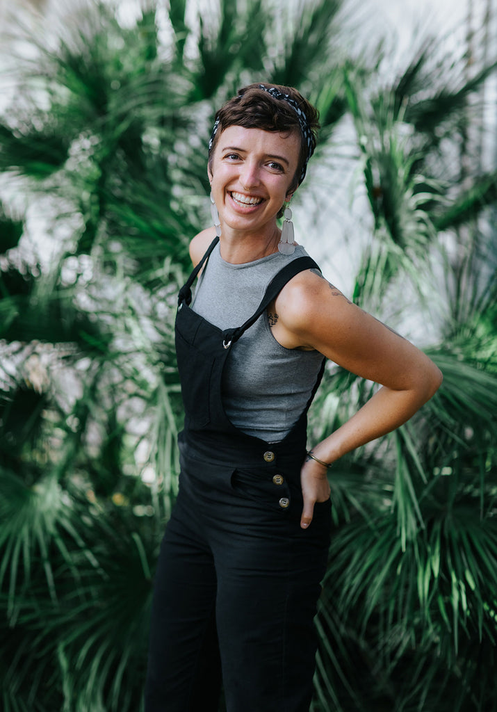 Jess is wearing the RJ Overalls in black over the Ribbed Crop Top in grey in front of a large leafy plant.
