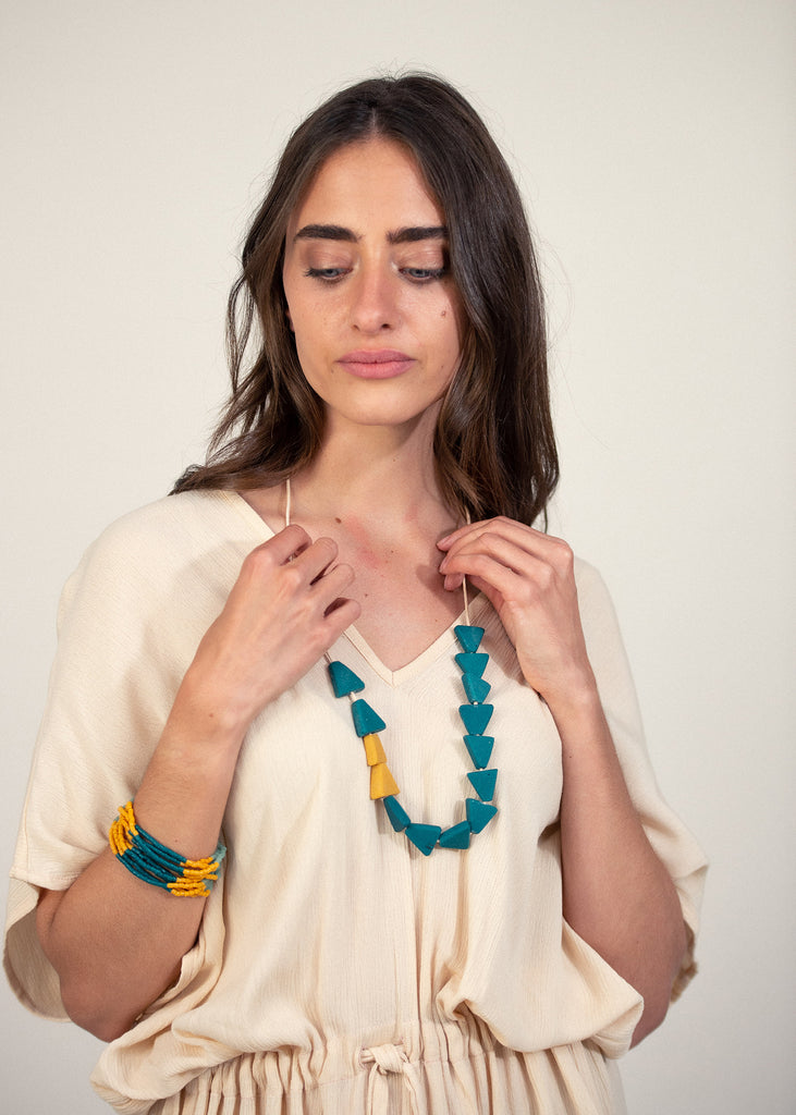 Justine is wearing tonlé's otres dress with a recycled glass fast forward necklace