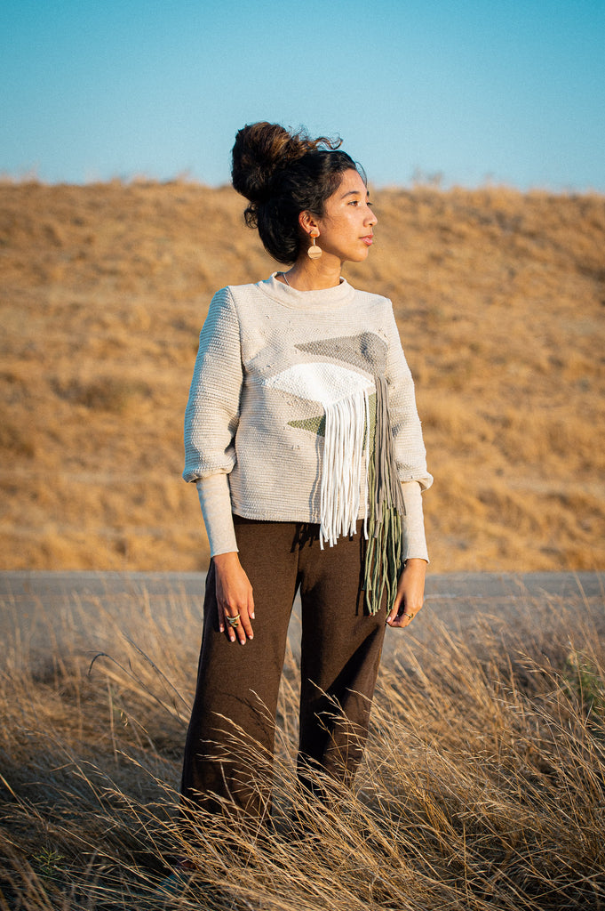 Kristy wearing an olive and green handwoven fringe sweater in front of a blue sky and yellow grasses