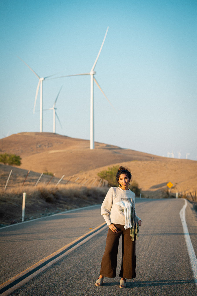 Kristy standing in front of wind turbines wearing a fringe sweater and chocolate brown pants