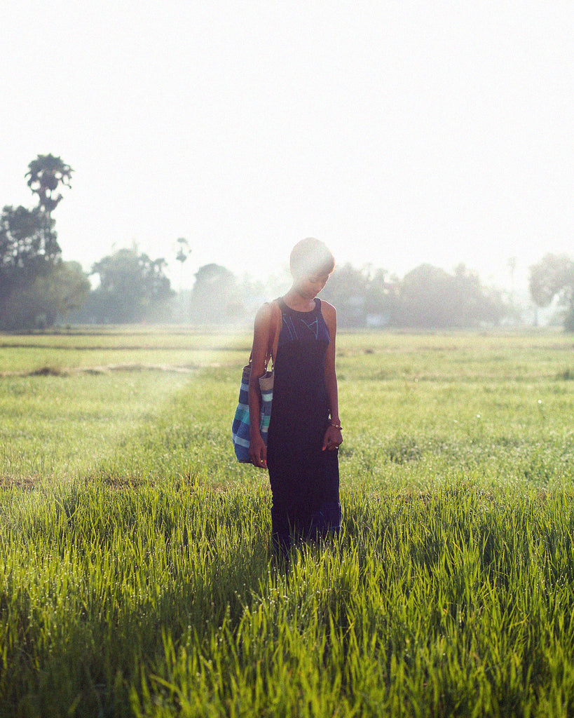 Vichka standing in a rice field in Cambodia at sunrise wearing clothing by tonlé