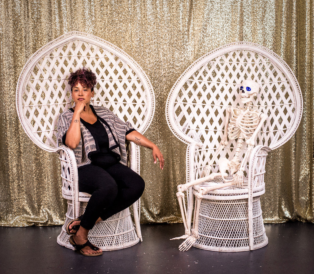 Woman sitting in a white chair with a skeleton
