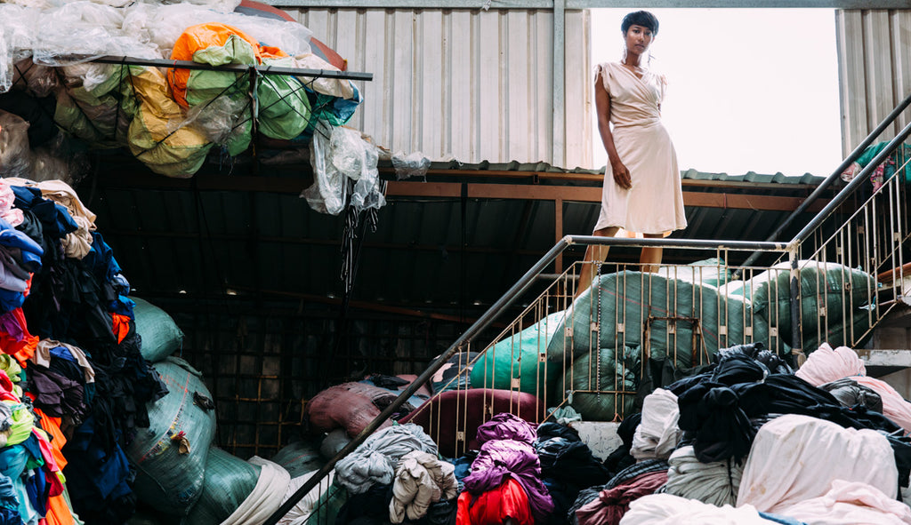 Woman standing in a pile of remnant fabrics