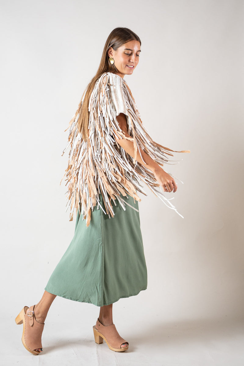 The swing of the fringe and drape of the shoulder is seen here in a side view of our Amara vest in natural.