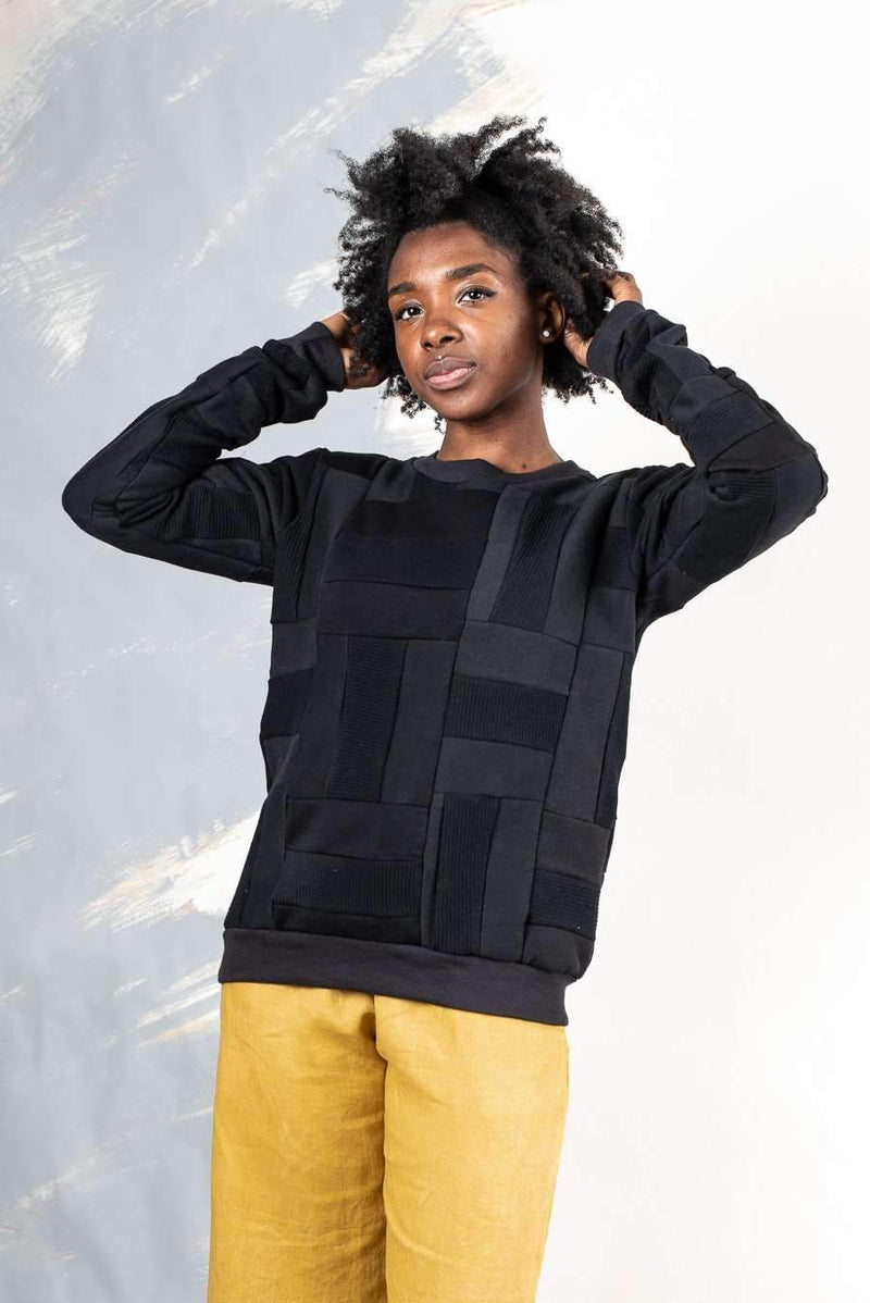 Black Angkor crew neck sweatshirt sustainably made from reclaimed jersey in a unique patchwork design.