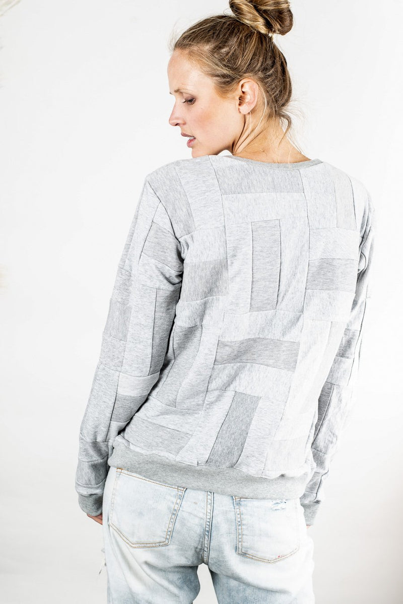 Back view of Angkor crew neck sweatshirt that shows the patchwork pattern used throughout this zero waste fashion piece.