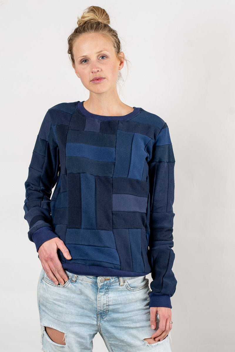 Our navy Angkor crew neck sweatshirt has a patchwork design that highlights our zero waste process.