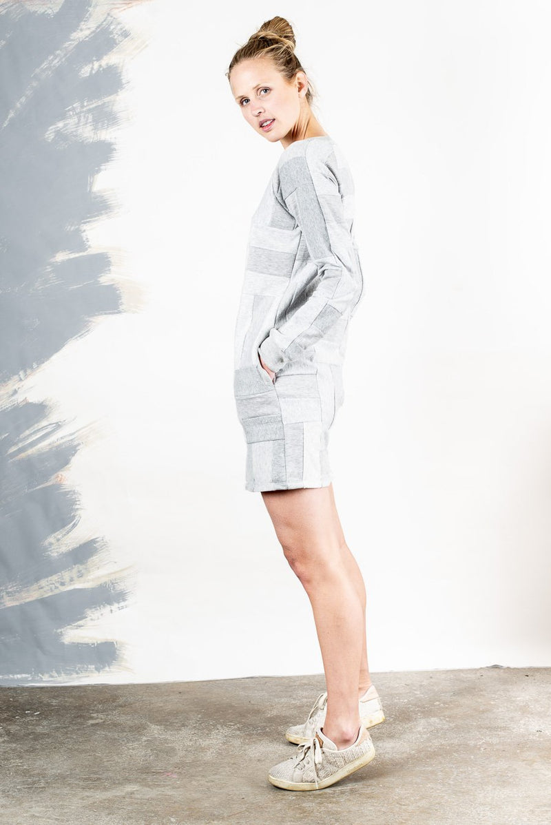 A side view of our ethically made sweatshirt dress, casually styled with sneakers.