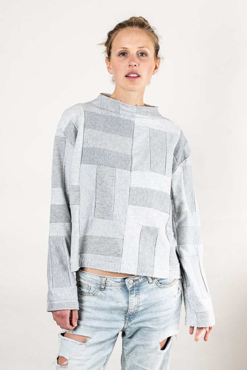 Our Angkor sweatshirt, seen here in grey, has a mock neck with a stylish raw edge.