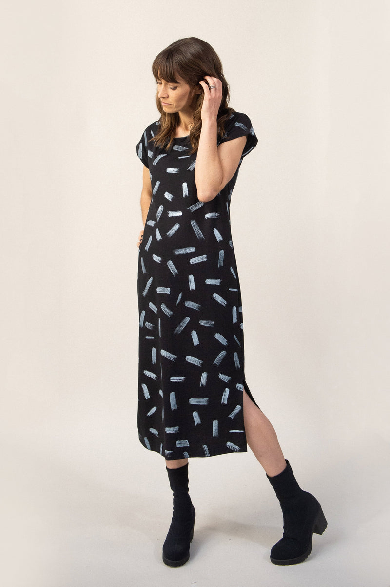Our Anja dress is a long t-shirt dress. Seen here in black with a dash print. Made from reclaimed jersey as part of our unique zero waste process.