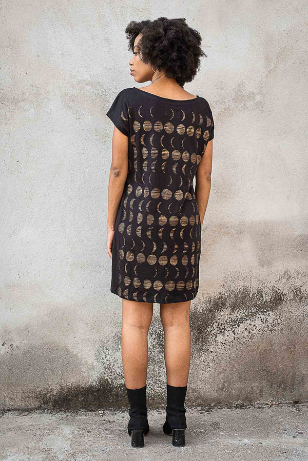 A back view of our ethical fashion t-shirt dress in black with a moon phase print.