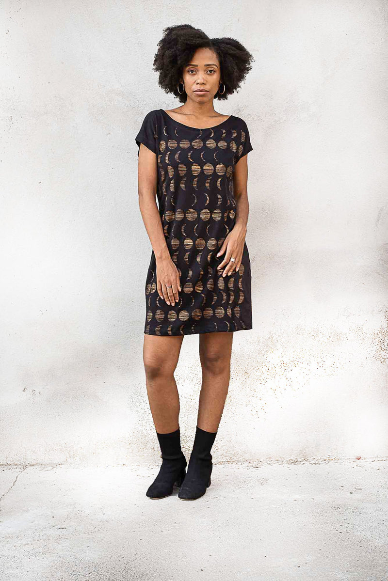 A front view of the basic t-shirt dress with a moon cycle print  on black jersey. Made from reclaimed textiles in our zero waste process.