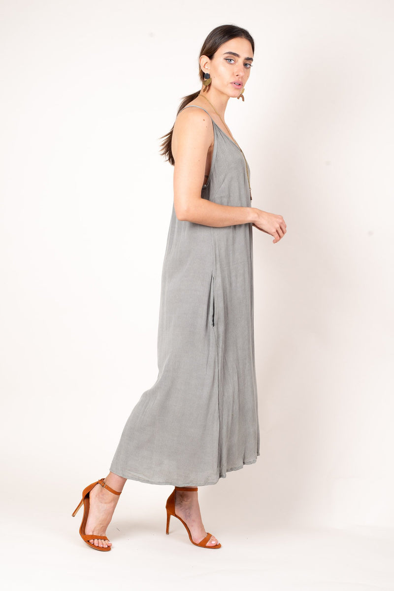 A side view of our grey midi dress, with deep pockets for comfortable sustainable style.