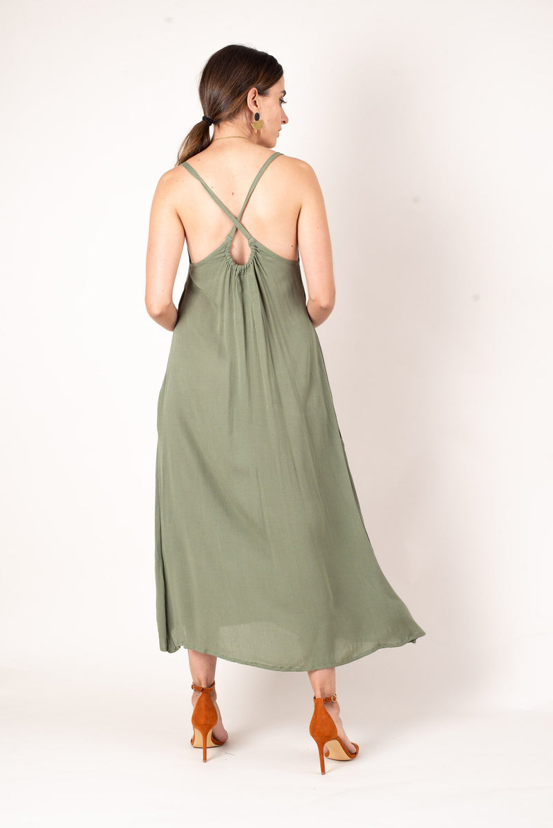 A back view of our moss green zero waste midi dress featuring an elegant cross strap key hole detail.