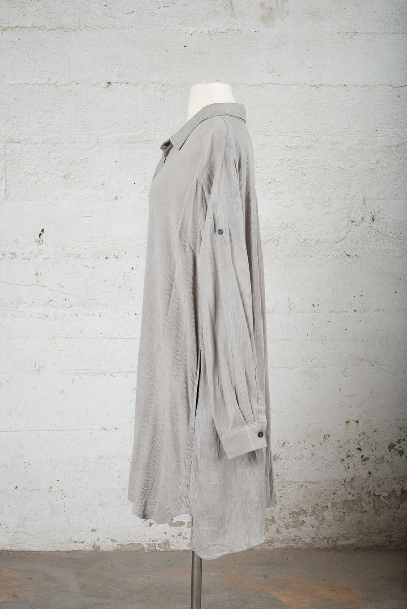 Side view of a preworn garment with the sleeves down.