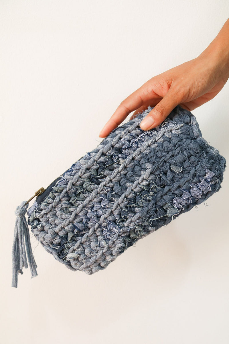 A detail shot of the ethically made crocheted clutch in denim blues.
