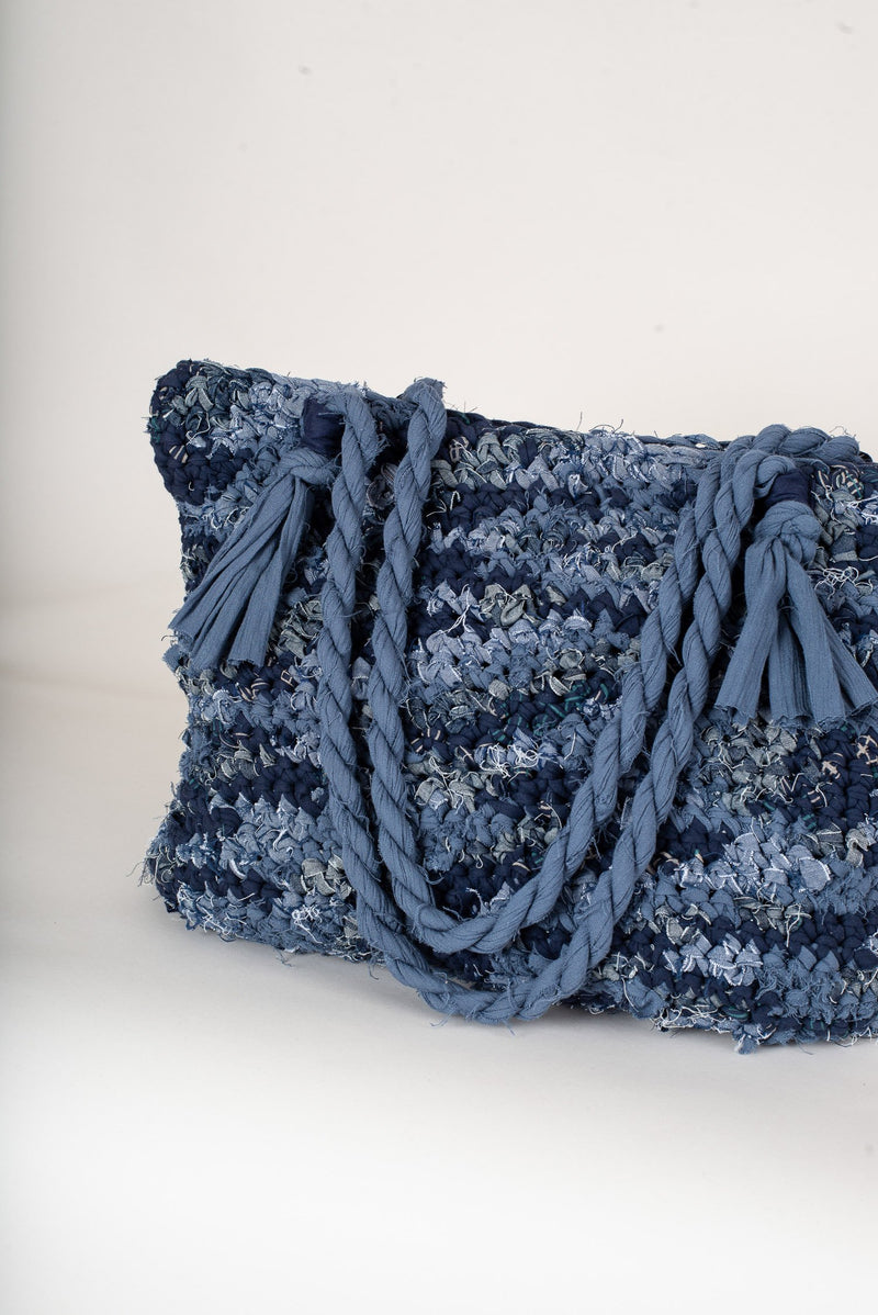 A detail shot of the texture in our ethically made crocheted tote in denim blues.