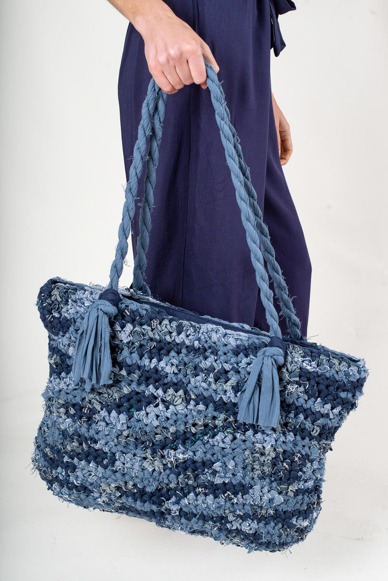 This crocheted tote bag is made from scraps of reclaimed fabric in our unique zero waste process.