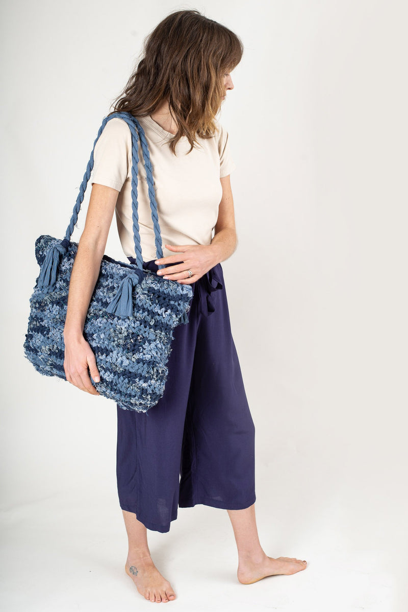 A photo of the crocheted tote on a model that shows the scale of the bag.