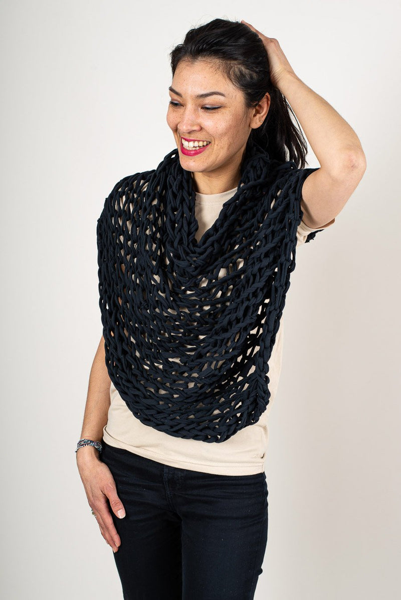The Maleng poncho can be draped many different ways over the body, from side to front, as seen here in black.