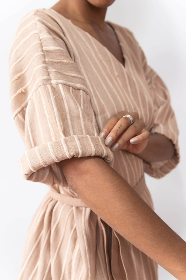 The sleeves on the ethically made RJ wrap top can be cuffed, as seen here.