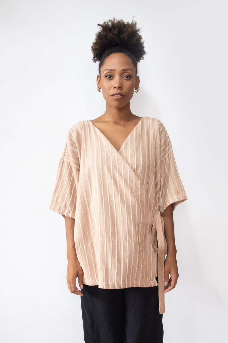This image of the handwoven RJ wrap top in palm shows the piece styled loosely with the tie at the side.