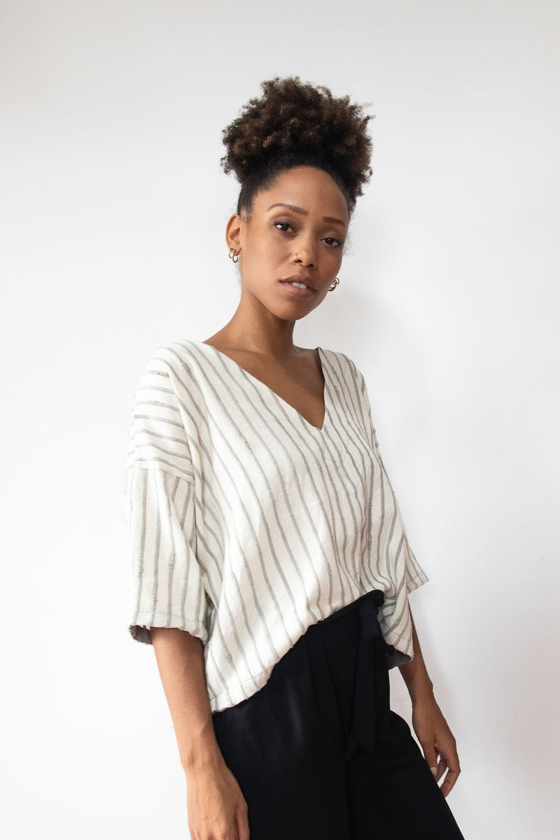Our ethically made Veha top is styled tucked into a skirt in this image.