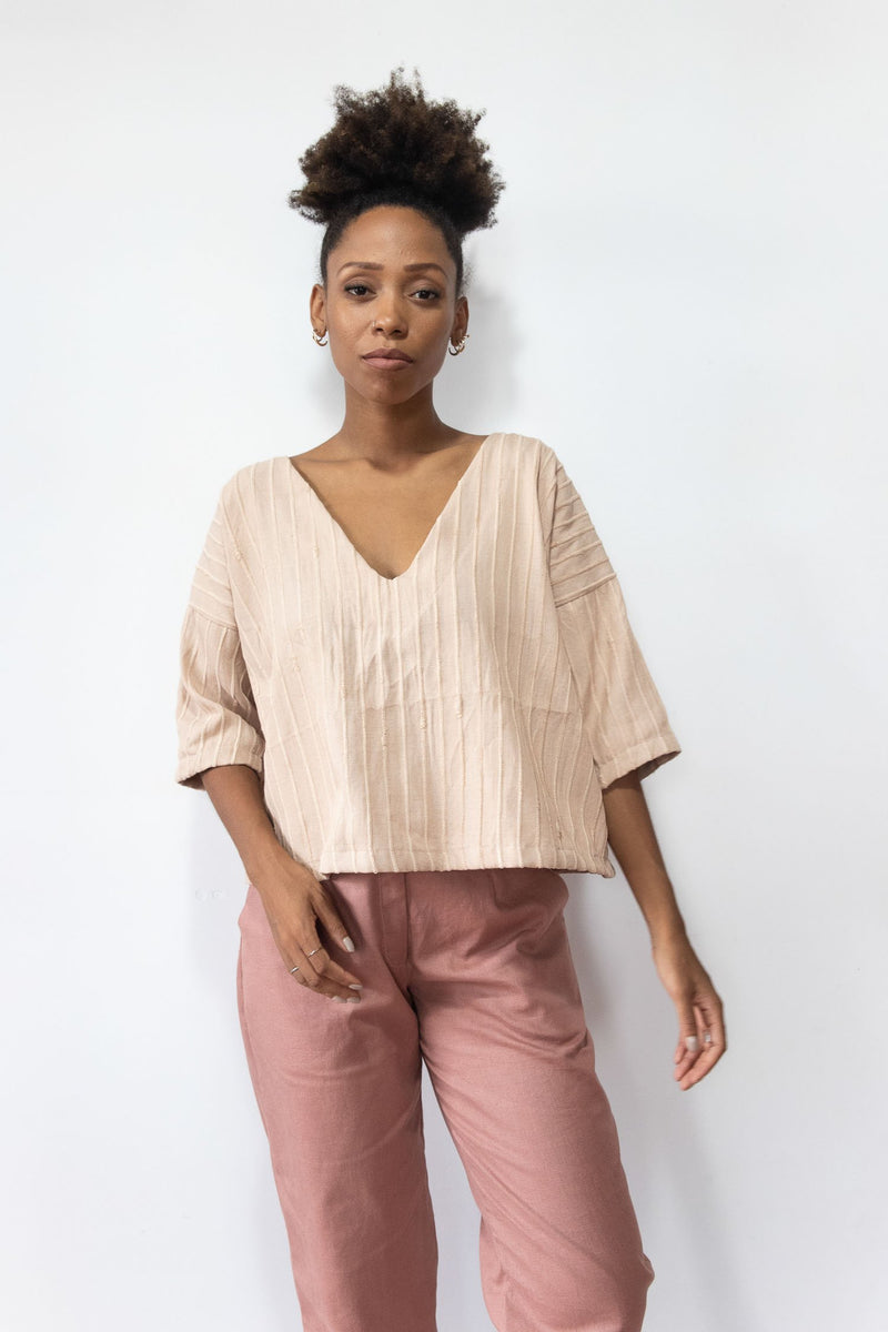 Our handwoven Veha top, shown here in palm, has an elegant v-neck.