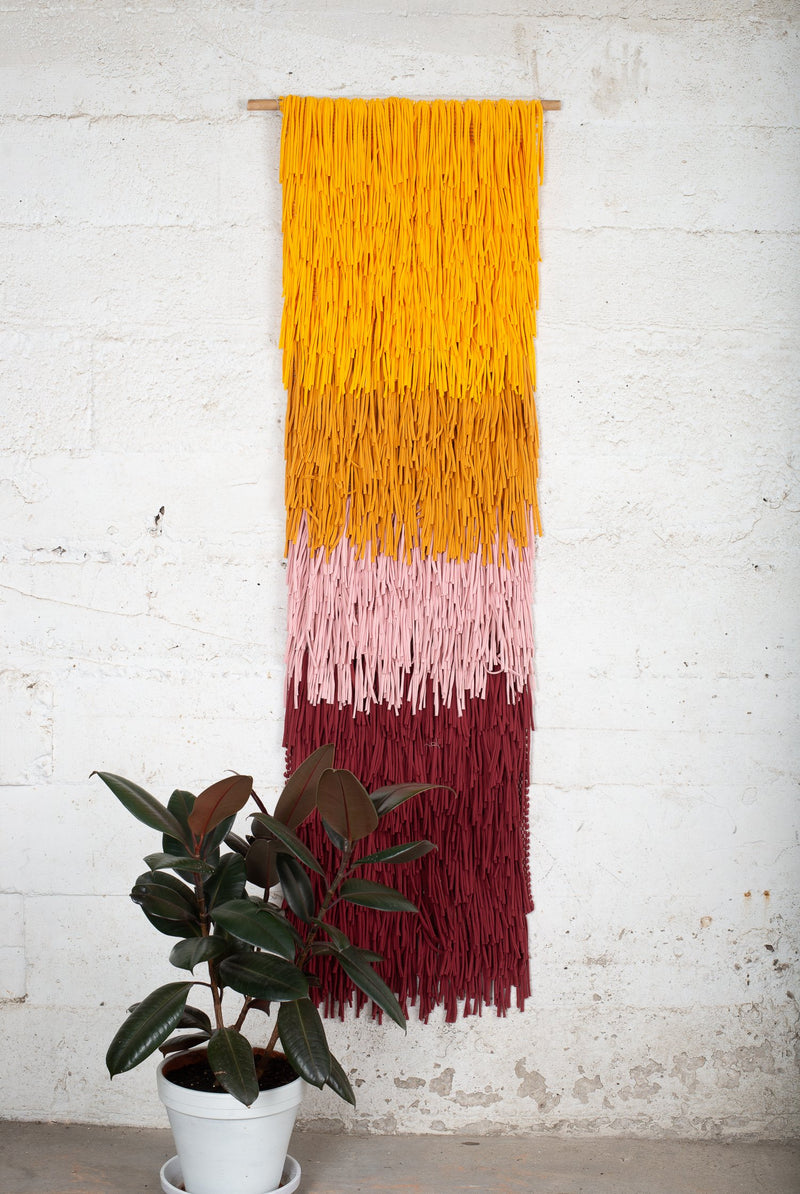 This handwoven wall hanging is made from remnants of reclaimed textiles in our zero waste process.