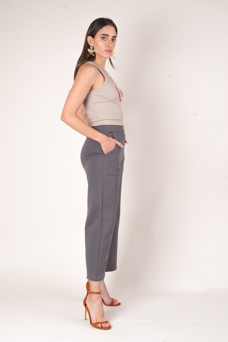 A side view of the warm grey jorani pants show off pockets and a high waistline for ultimate ethical comfort.