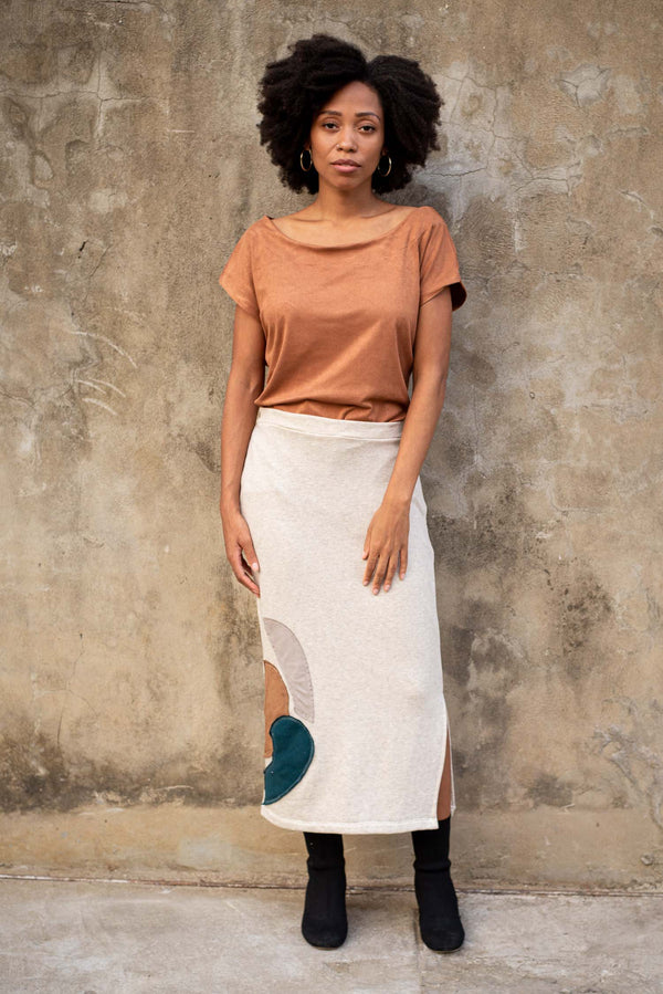 Our sustainably made Jorani skirt is seen here in cream with a modern graphic applique near the hem.