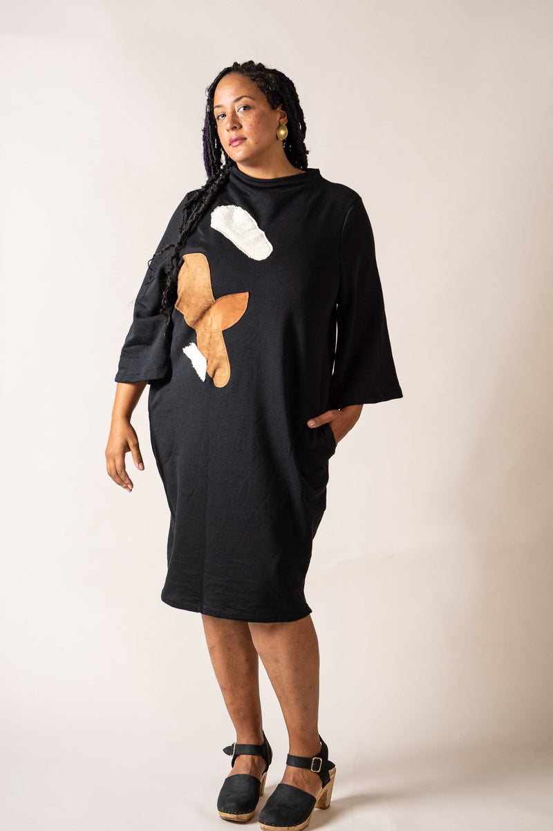 This version of our sustainably made sweatshirt dress, seen here in black, has a modern graphic applique on the front.