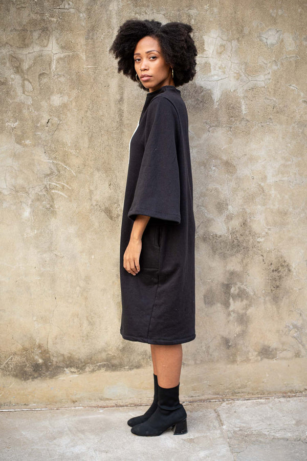 A side view of the Jorani sweatshirt dress that shows the wide sleeve and side pockets.