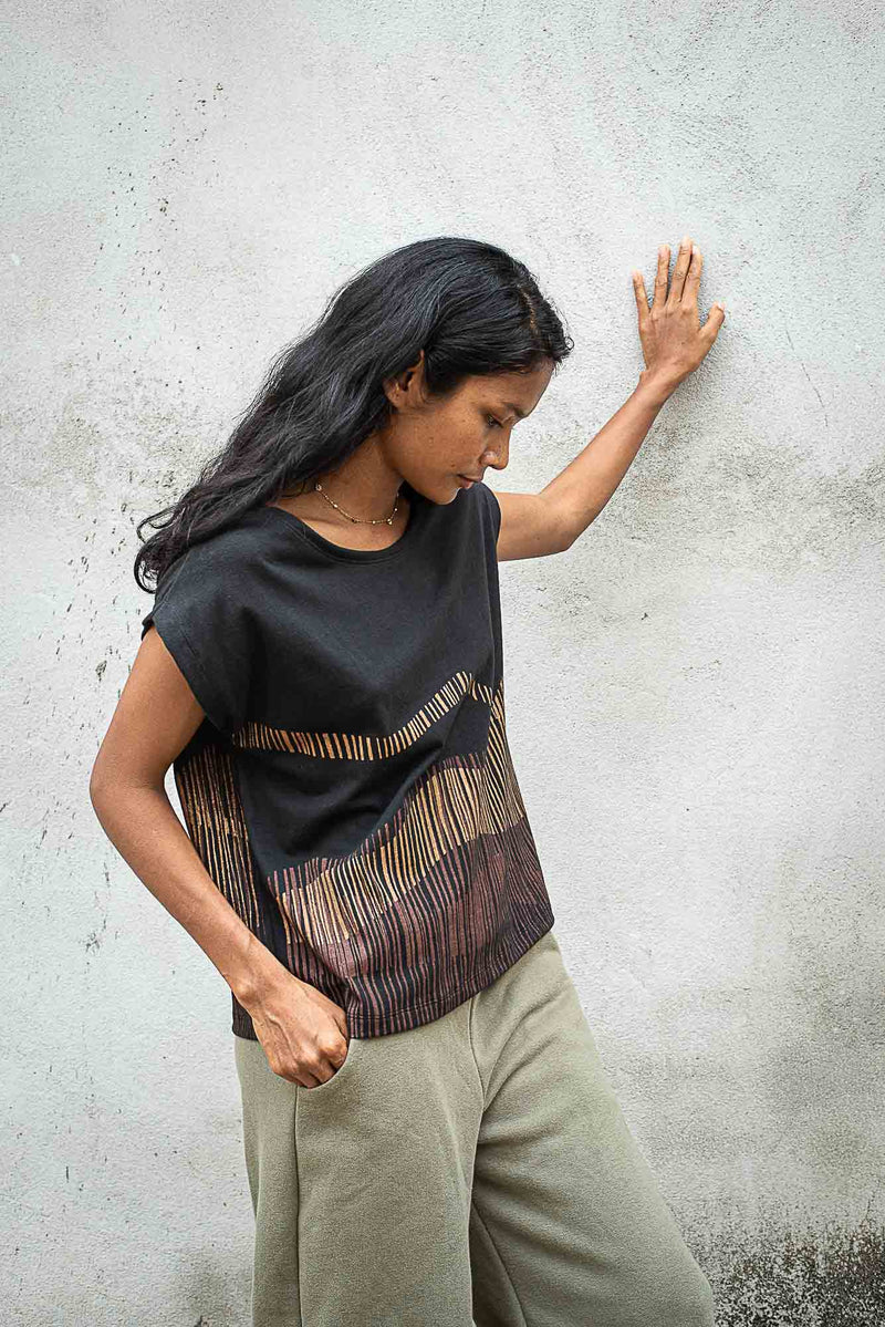 A side view of our fair fashion Keang top with a mountain print, that shows the cut of the sleeve.