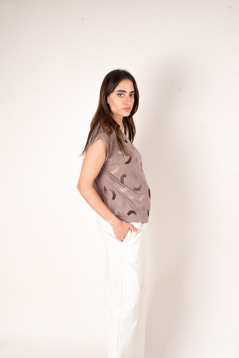 A side view of the sustainable taupe jersey boxy t-shirt top with hand-painted with a softly curved dash.