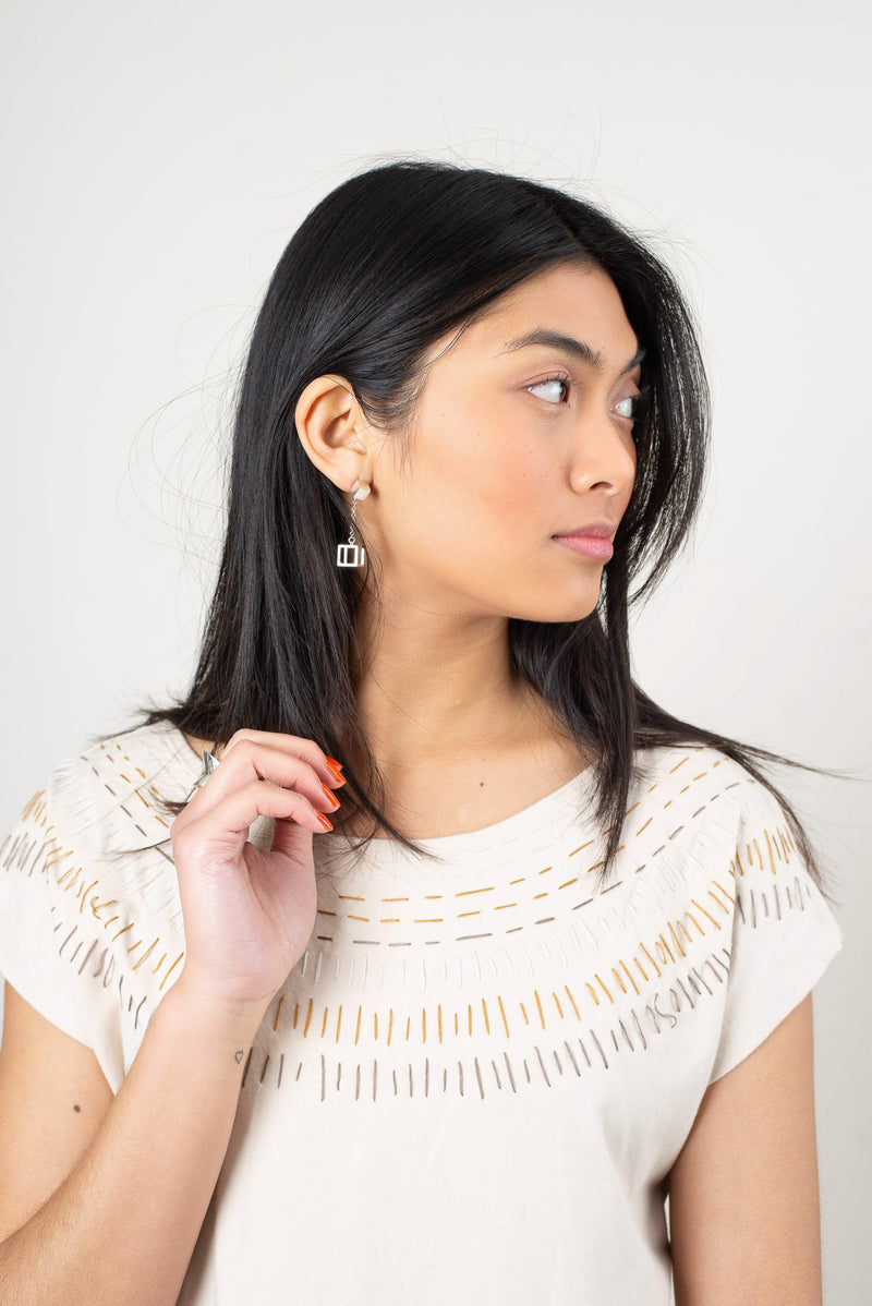 Our sustainably made Keang top in cream, with a sunburt pattern embroidered around the neckline.