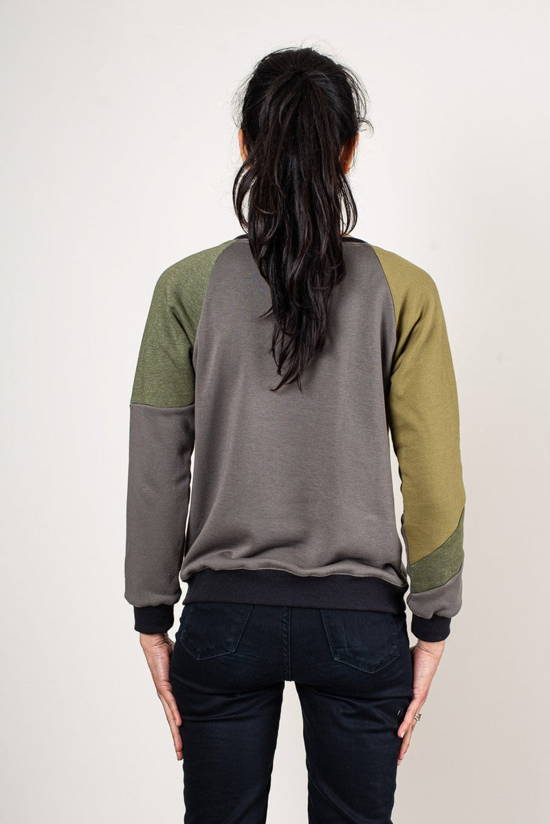A back view of the Kendal sweatshirt in olive that shows the graphic pattern pieces of reclaimed sweatshirt fleece.