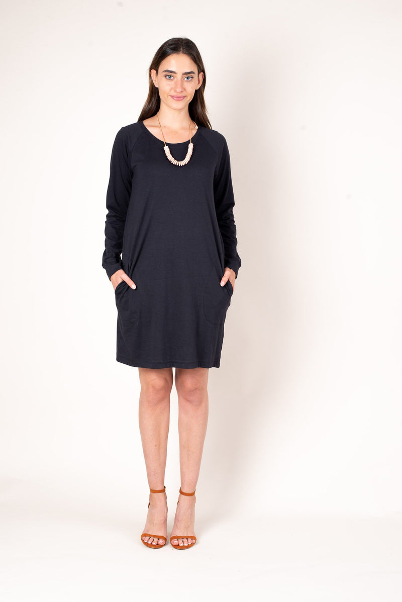 A front view featuring the pockets of our sustainable long sleeved khema dress shown here in back jersey.