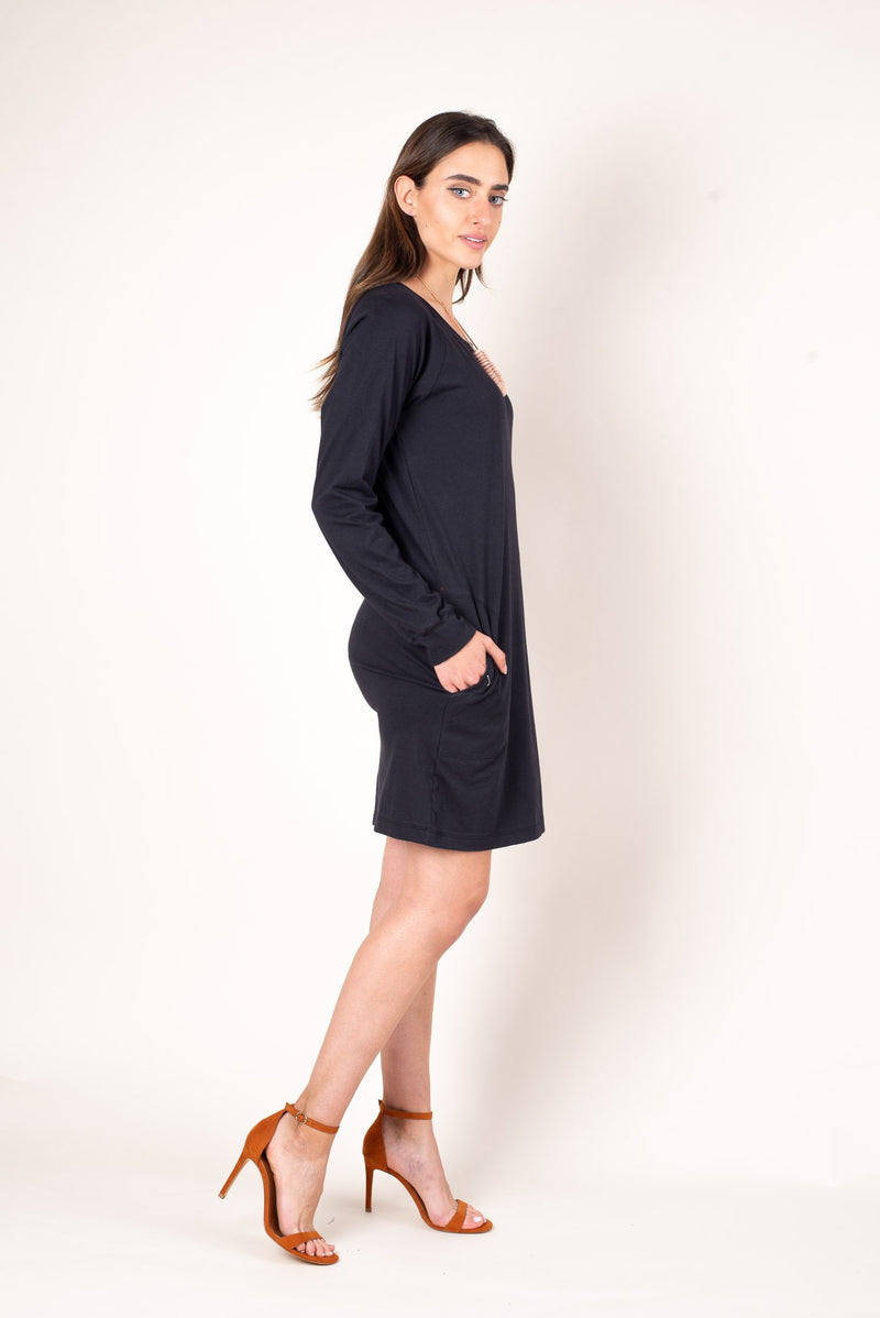 A side view of the black khema dress, featuring a loose flattering fit with long raglan sleeves.