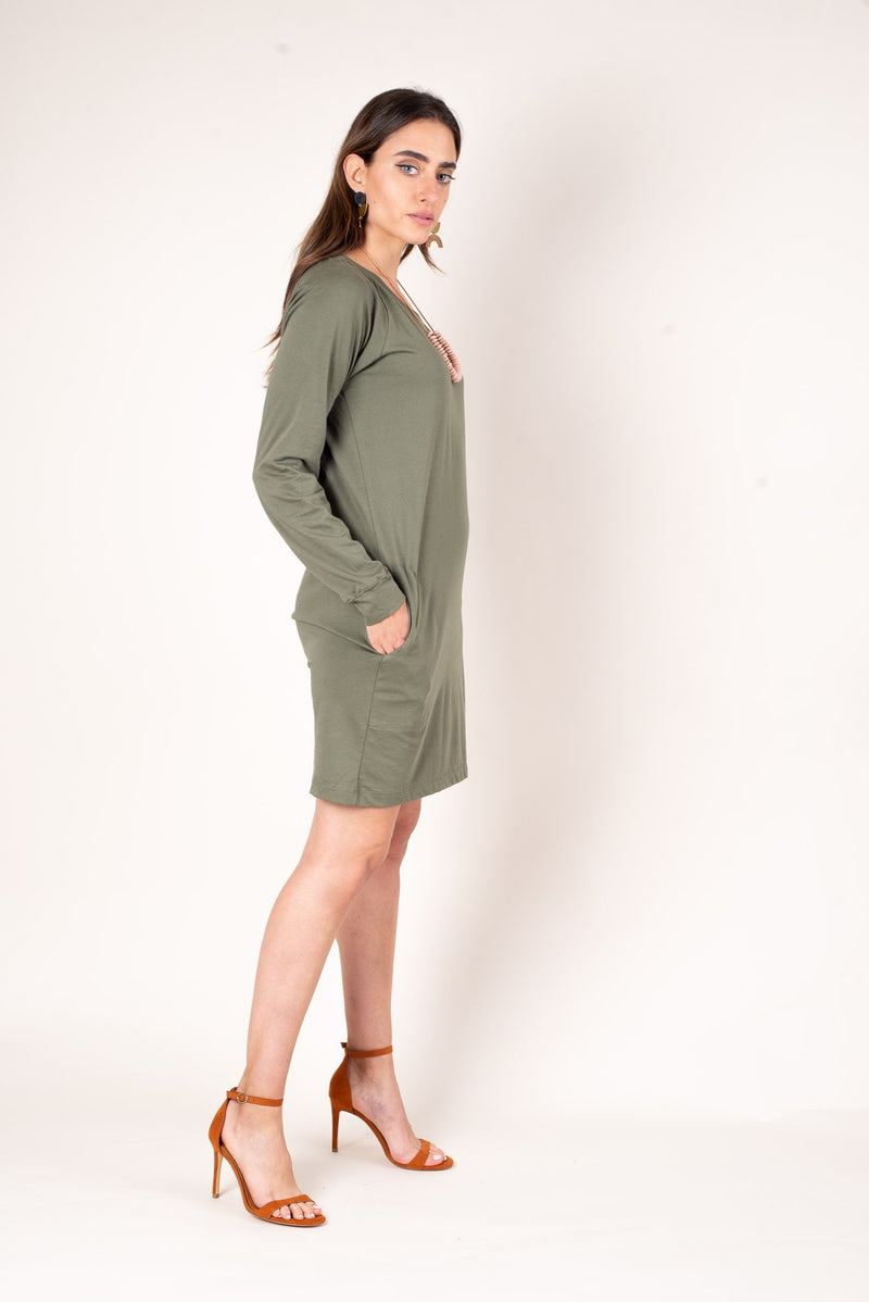 A side view of our comfy cozy sustainably made knee length jersey dress. Shown here in moss and dressed up with heels and a statement necklace.