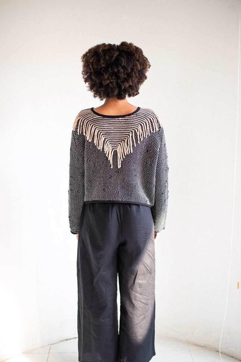 A back view of the Kiri sweater in palm and black. This fair fashion sweater has an eye-catching fringe design on the back as well as the front.