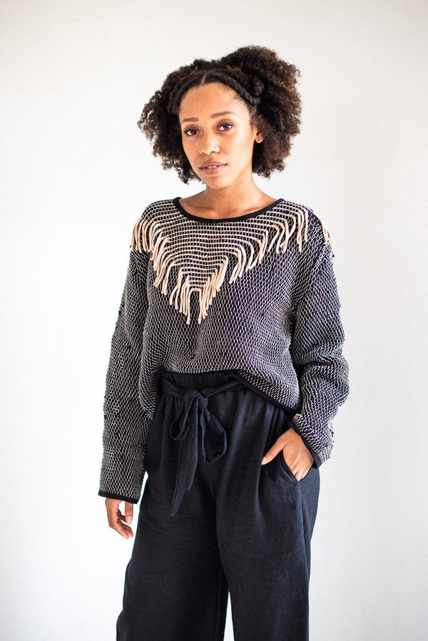 The Kiri sweater, seen here in palm and black, is handwoven from reclaimed textiles as part of our zero waste process.
