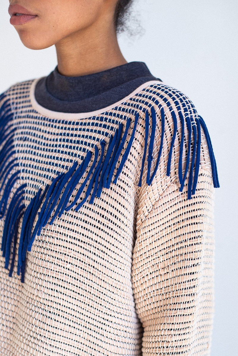 A detail of the ethically made Kiri sweater that shows the fringe around the neckline.