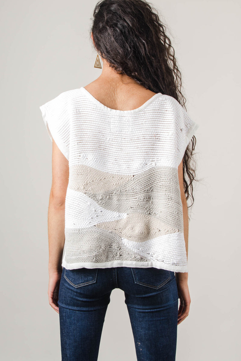 A rear view of the sustainably made landscape crop top that shows how the handwoven design continues on to the back of the top.