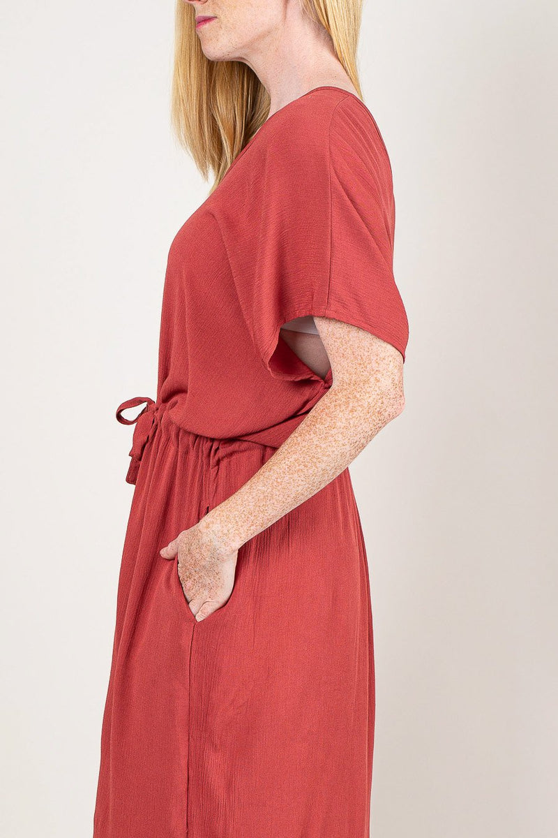 This side image of our kaftan in pink clay shows a detail of the pocket, drawstring waist, and sleeve opening.