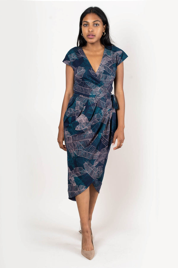 Our ethically made lotus dress, seen here in navy with a banana palm print, is a wrap dress that's as easy to wear as your favorite t-shirt.