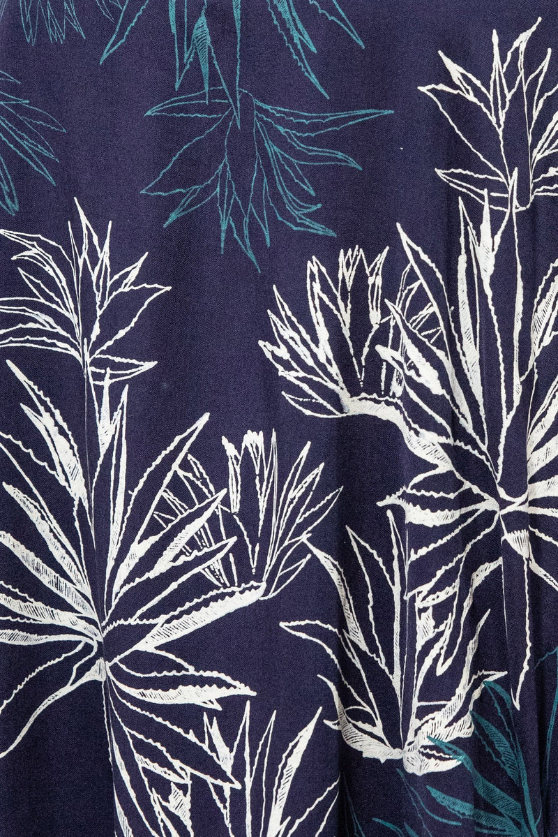 A detail view of the intricate hand-printed cactus pattern on the navy jersey in our sustainably made lotus dress.