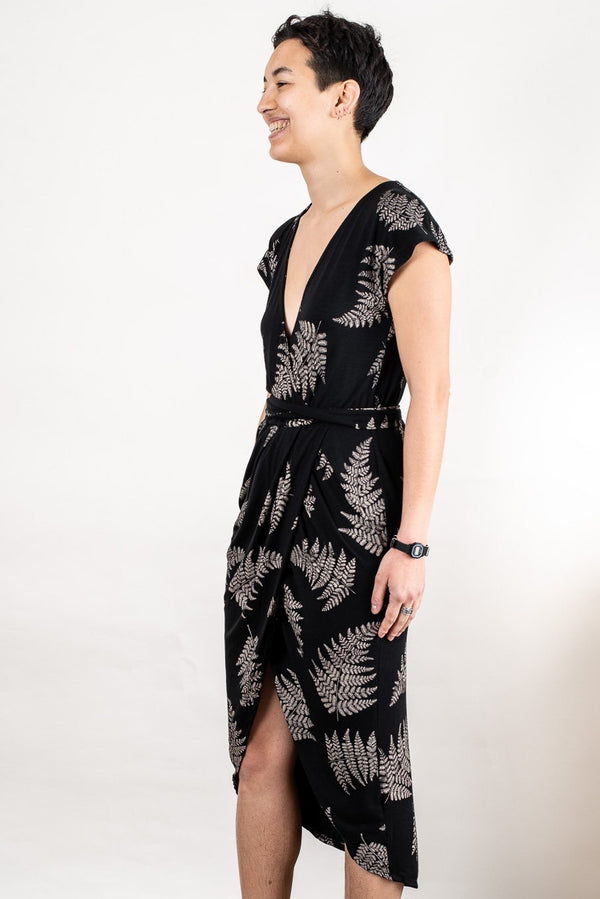 A side view of our ethically made lotus dress in black with a fern print that shows the drape of the wrap skirt.