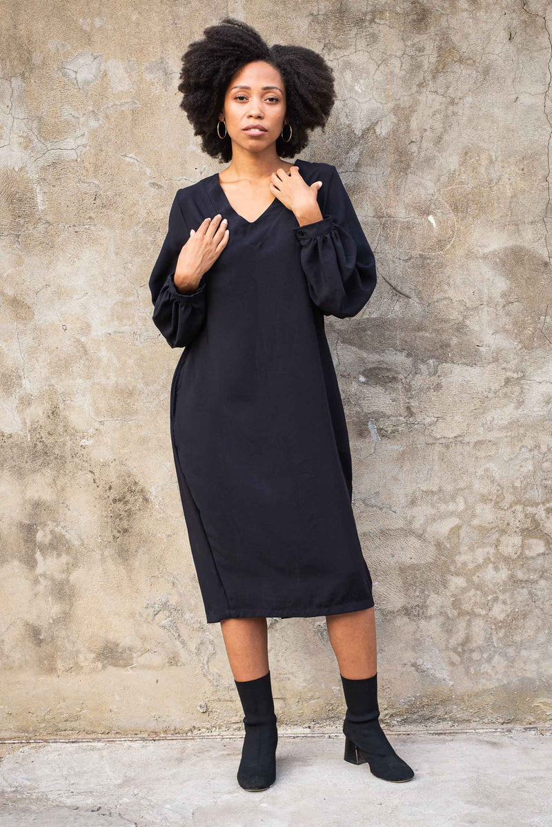 Our sustainably made Maly dress, seen here in black, has an elegant v-neck.
